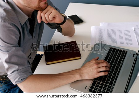 Close-up of unrecognizable businessman working on laptop at workplace