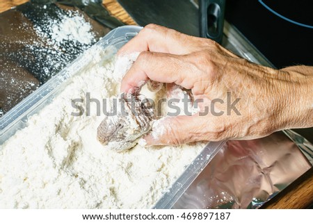 Close-up of unrecognizable man preparing fish for frying
