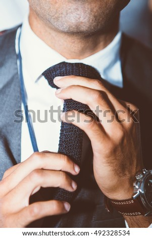 Close-up of unrecognizable man with bristle tying knit black tie
