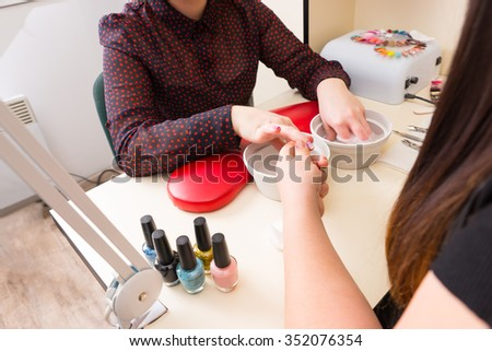 Close Up of Unrecognizable Woman Getting Manicure in Spa - Manicurist Preparing Treat Nails of Female Client with Hands Soaking in Water - stock photo