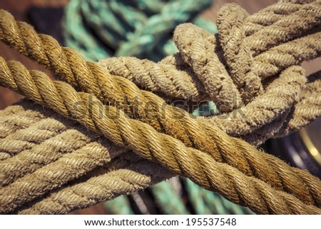 Close-up of used vintage marine ropes with nautical knot on old sailing vessel. - stock photo