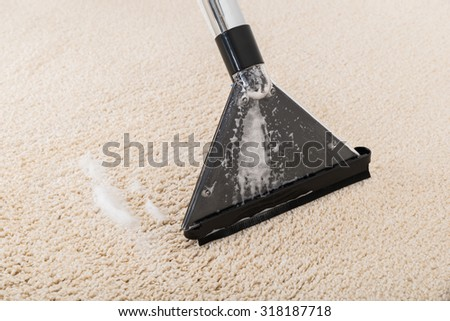 Close-up Of Vacuum Cleaner On Wet Rug - stock photo