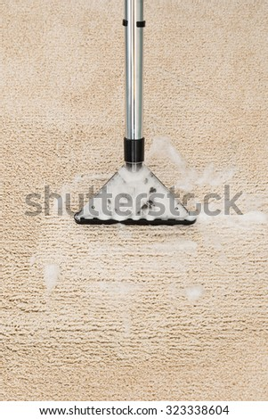 Close-up Of Vacuum Cleaner With Foam Over Carpet - stock photo