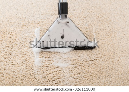 Close-up Of Vacuum Cleaner With Foam Over Wet Carpet - stock photo