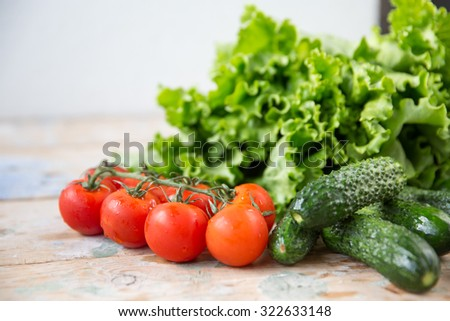 Close up of various colorful raw vegetables. Red cherry tomatoes and cucumbers, Lettuce salad on the wooden table. - stock photo