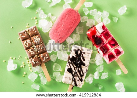 Close-up of various delicious popsicles with ice on green background - stock photo