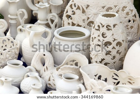 close-up of various dishes of white clay handmade in natural light - stock photo
