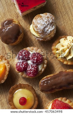 Close up of various French cakes on a wooden board - stock photo