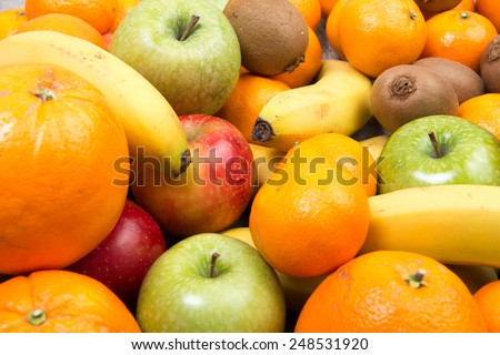 close up of various seasonal fruits with oranges,bananas, apples and kiwis - stock photo