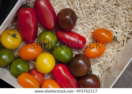 Close up of various tomato in a crate on a market stall