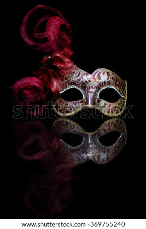 Close up of venetian mask with feathers and rhinestones. Art work. Isolated on black background.
