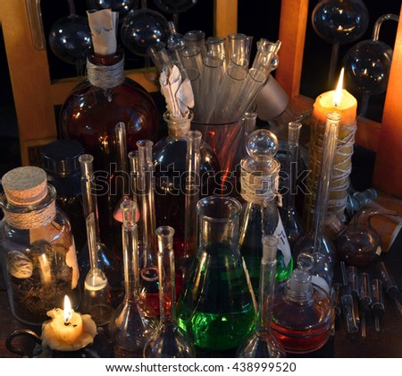 Close up of vintage bottles, flask and candles in alchemy laboratory.  Old pharmacy, esoteric or alternative medicine concept. Black magic and occult objects, medieval alchemist ritual - stock photo