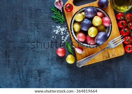 Close up of vintage cutting board with organic ingredients (potatoes, tomatoes, garlic and olive oil) over dark grunge background. Raw vegetables from garden for healthy cooking. Top view. - stock photo