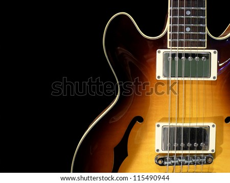Close-up of vintage electric jazz guitar on black background. - stock photo