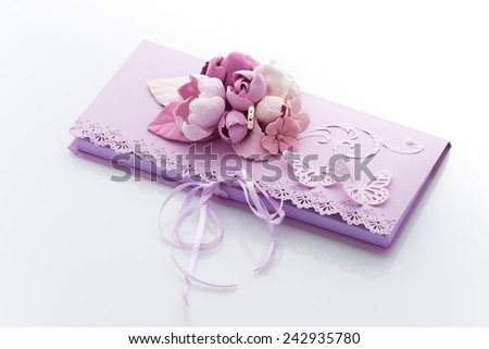 Close up of violet an invitation envelope decorated with flowers and butterflies - stock photo
