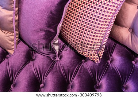 Close up of violet velvet sofa and cushions with vintage style.
