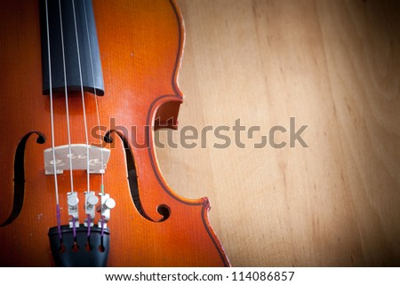 Close up of violin on the left  on wooden background
