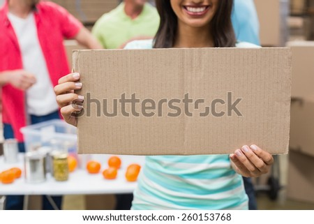 Close up of volunteer showing a poster in a large warehouse - stock photo
