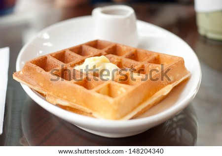Close up of waffle with butter topping on white plate