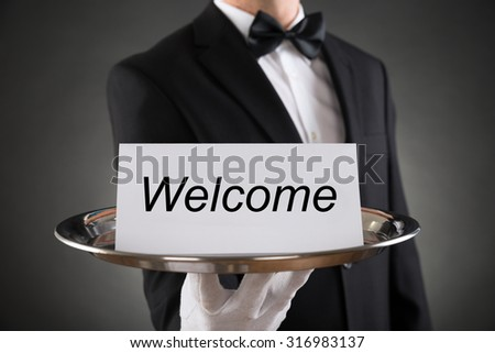 Close-up Of Waiter Holding Plate With Welcome Text On Paper