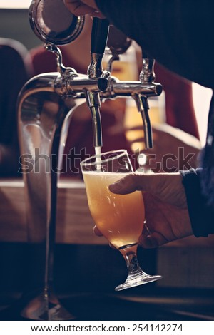 Close Up Of Waitress Hands Pouring Beer Into Glass