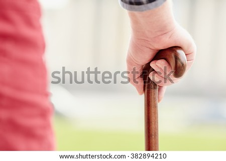 Close up of walking stick in senior male hand outdoors - recovery concept - stock photo