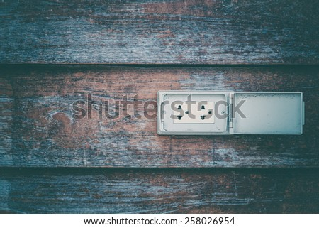 close up of wall made of wooden planks with plug socket  - stock photo