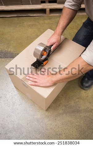 Close up of warehouse worker preparing a shipment in a large warehouse - stock photo