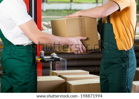 Close-up of warehouse workers with box, horizontal - stock photo