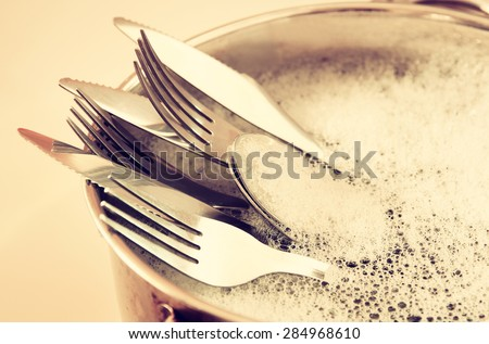 close up of washed dishes in the kitchen: silver spoons, forks and knifes. retro filtered image - stock photo