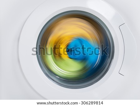 Close-up Of Washing Machine Door With Multicolored Clothes Rotating Inside