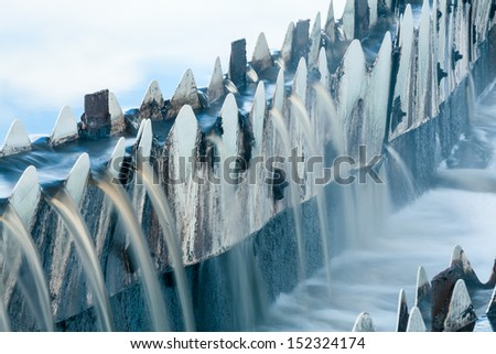 Close-up of waste water overflowing from round settlers, long exposure - stock photo