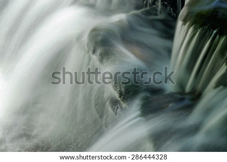 Close up of water cascading over moss covered stones and rocks - stock photo