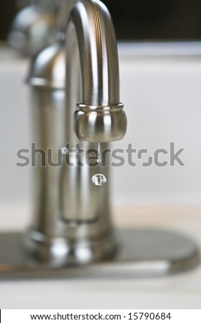 Close up of water dripping from a bathroom faucet.