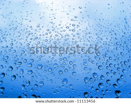 close-up of water drops on a blue glass surface