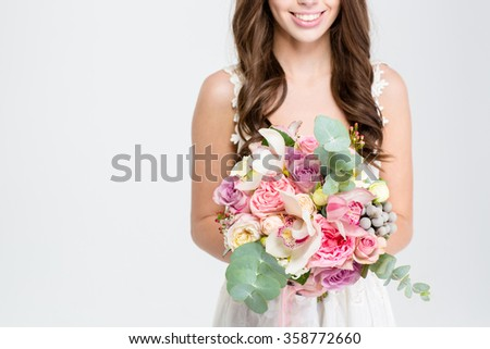 Close up of wedding bouquet of flowers holded by happy young bride with curly hair in white dress over white background - stock photo