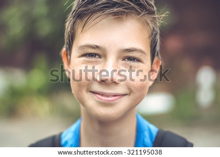 Close-up of wet child with freckles looking at the camera. As well as holding a backpack on his shoulders. - stock photo