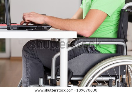 Close-up of wheelchair worker using computer, horizontal - stock photo
