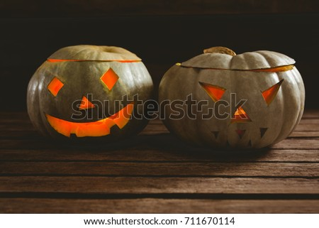 Close up of while illuminated jack o lanterns on table during Halloween