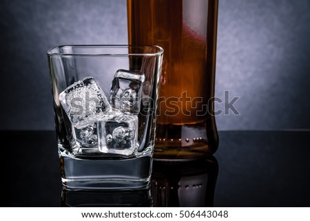 close-up of whiskey with ice cubes in glass near bottle on black background, cold atmosphere, time of relax with whisky
