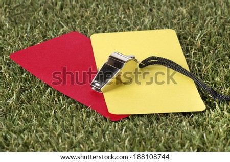 Close-up Of Whistle With Red And Yellow Card On The Field - stock photo