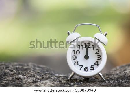 Close-up of white alarm clock on rock. - stock photo