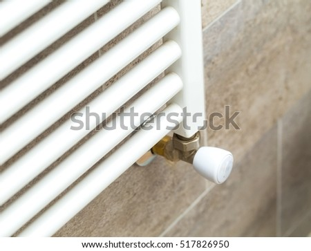 Close up of white bathroom heater on wall with tiles. Bathroom hydraulic equipment.