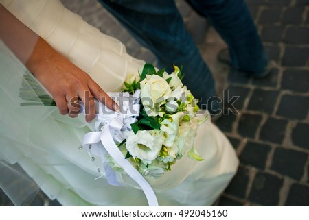 Close-up of white bouquet held by a bride behind her delicate skirt