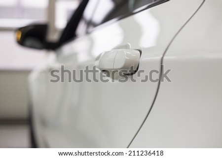 Close-up of white car in repair store - stock photo