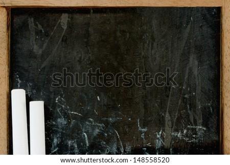 Close-up of white chalks on old empty blackboard - stock photo