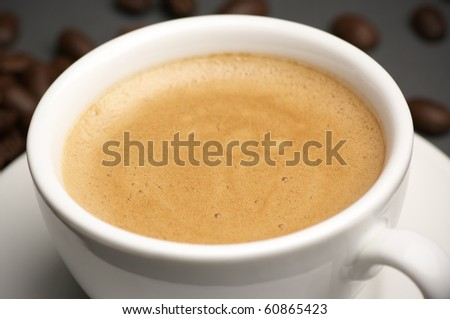 Close-up of white cup of coffee with froth. - stock photo