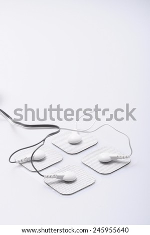 Close up of white electrodes and electrical stimulation device - stock photo