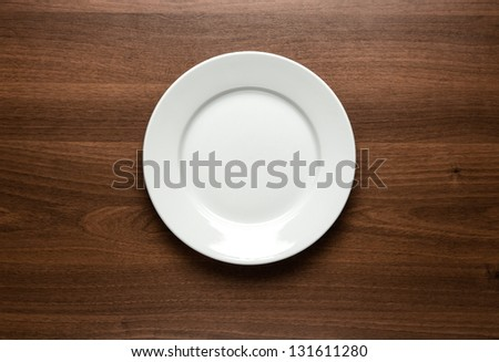 Close up of white empty plate at the wooden table with copy space - stock photo