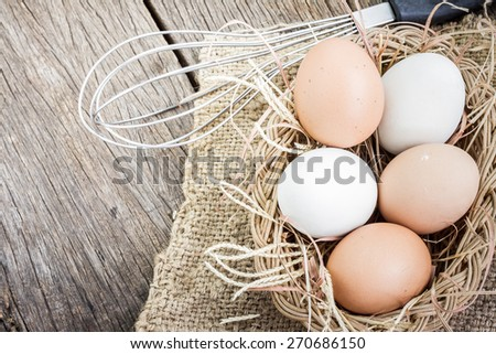 Close up of white fresh egg on basket with brown burlap on wooden floor - stock photo